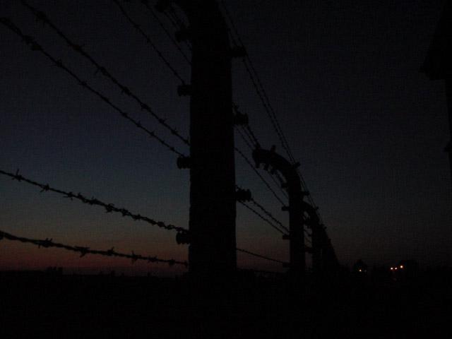 Foto der Frontseite der Aussensicherung des Konzentrationslagers Auschwitz - Brikenau bei Nachteinbruch 2005