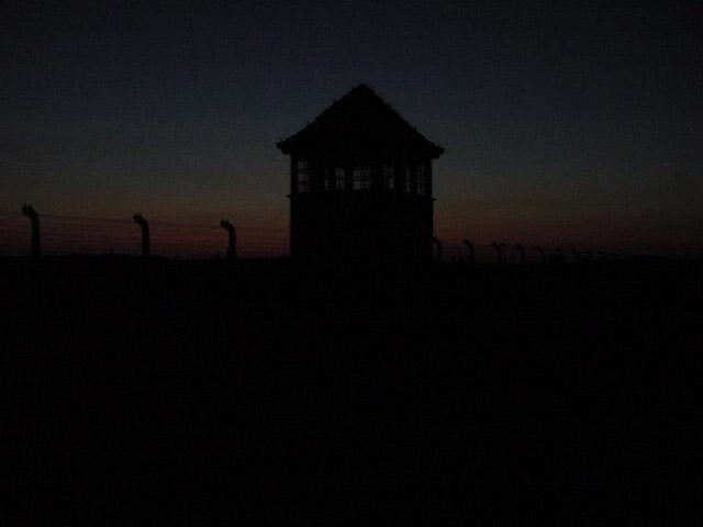 Foto der Frontseite des Konzentrationslagers Auschwitz - Brikenau mit Wachturm der SS bei Nachteinbruch 2005